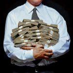 Man holding piles of money