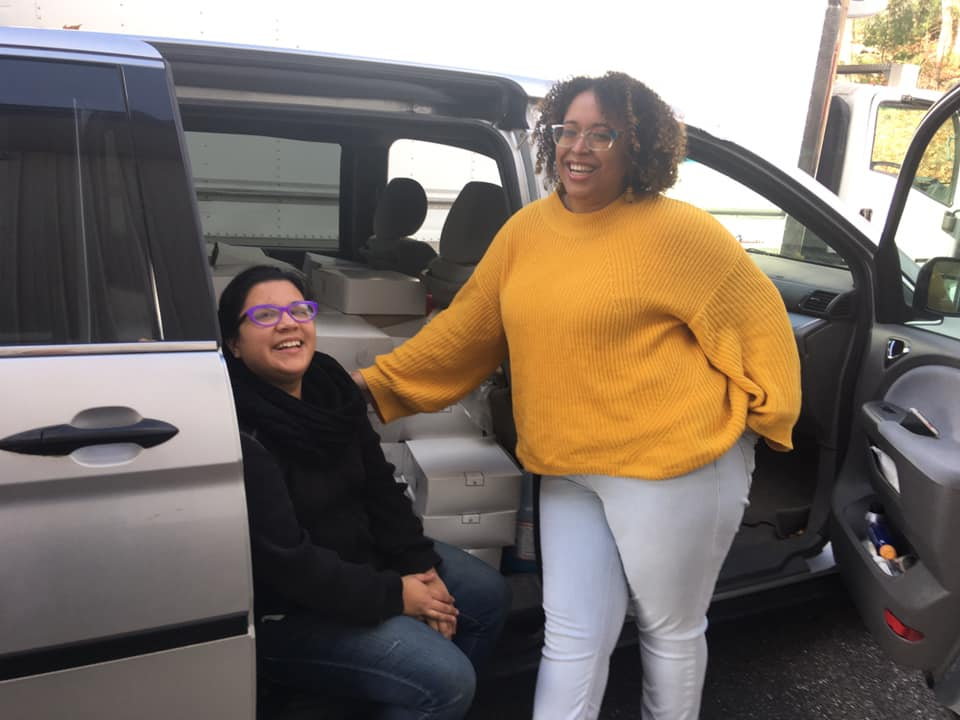 Rhea and Diana posed next to an open van filled with boxes of pie.