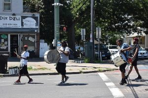 Four men holding marching drums walk down the street in Newhallville.