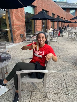 Robi Frederick sitting on a chair outside giving a thumbs up